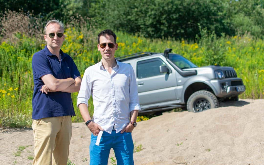 The photo shows Moritz and Sascha the founders of Bareways in summer with sunglasses. They are standing on a sand hill, a Suzuki Jimny can be seen behind them.