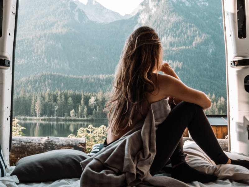 A woman is sitting on her bed in her van and is enjoying the view on a lake.