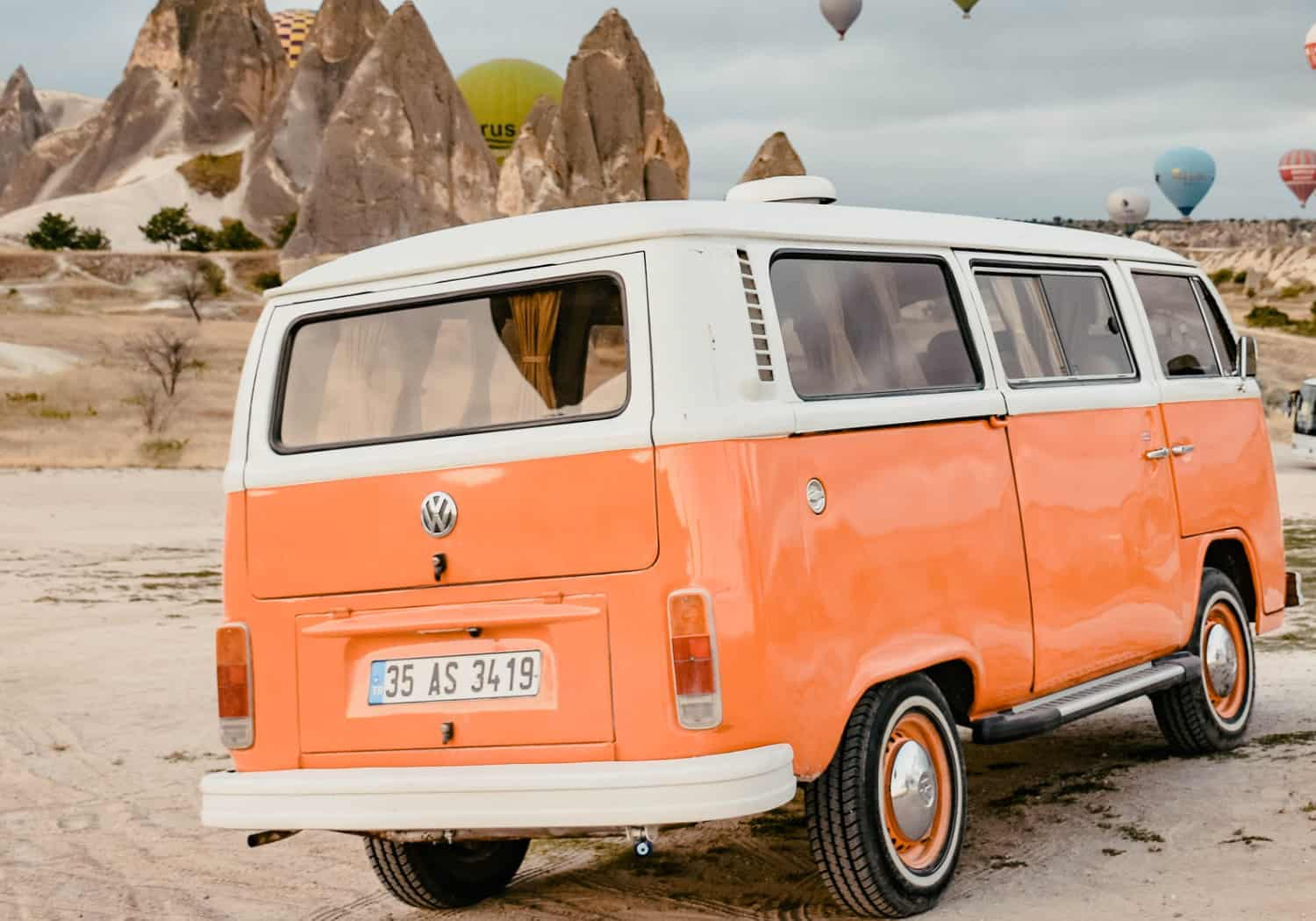 A orange Volkswagen stands on sand. In the background are rocks and hot-air-balloons.