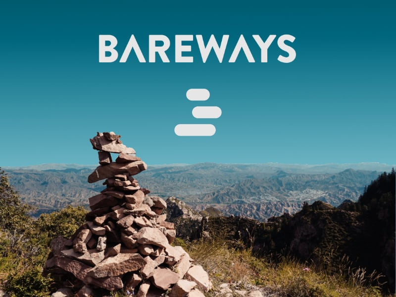 Top startups. Stone cairns in fron. In the Background a valley and blue sky with the Bareways logo. We love to explore the world by vehicle.